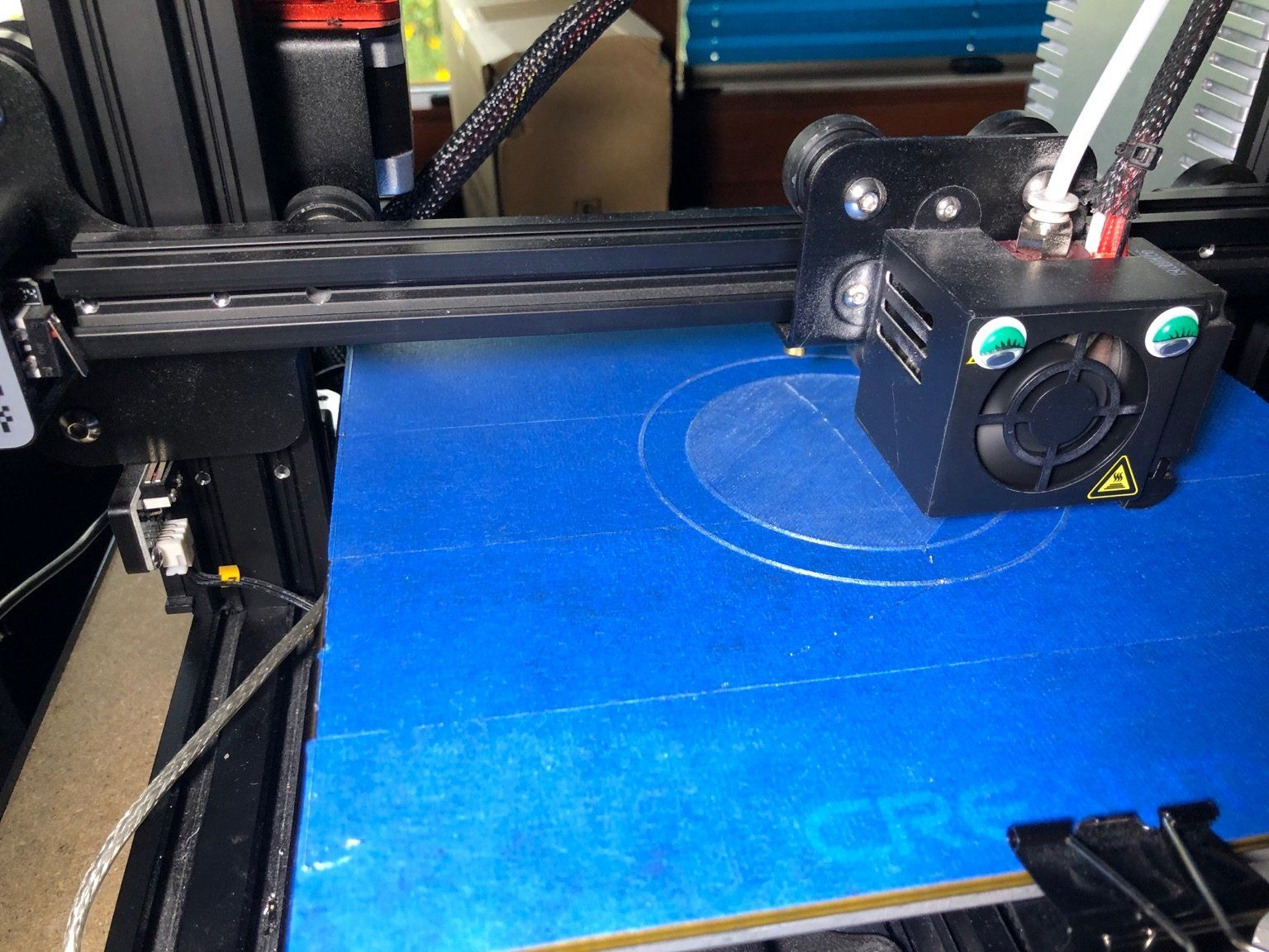 3D printer printing the flexible tin can lid on blue tape. The tape is there to make it stick to the build plate.